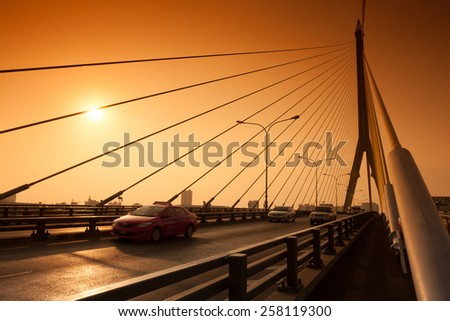 Traffic on suspension bridge at sunset.