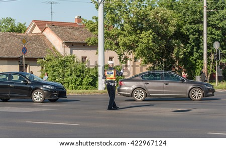 Traffic policeman directing cars in a crossing road, detail - stock photo