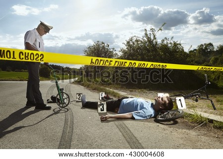 Traffic policeman observing place of accident with victim - stock photo