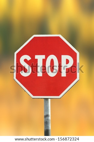 traffic red stop sign over beautiful faded autumn background
