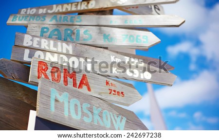 traffic road  sign including Moscow, Roma,London,Berlin,Paris, Rio de Janeiro on blue sky background in retro style - stock photo