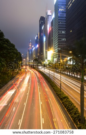 Traffic rushing at night along office towers in Wan Chai district on Hong Kong island, Hong Kong SAR.