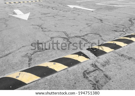 Traffic safety yellow and black speed bump in empty parking lot. Road markings of two way white arrows pointing opposite directions in background. Dirty cracked asphalt. Horizontal photo.  - stock photo