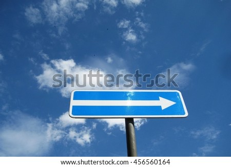 Traffic sign arrow pointing to the right direction against sky - stock photo