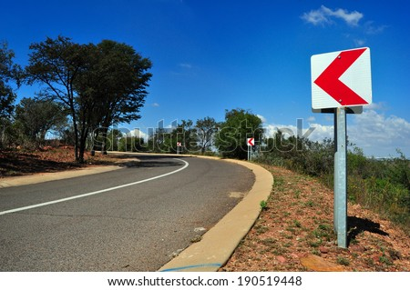 Traffic sign chevron against blue sky on a country road - stock photo