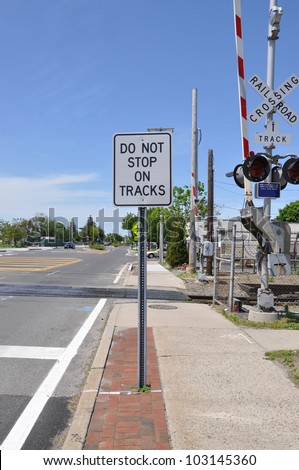 Traffic Sign Do Not Stop on Tracks Raised Crossing Gate - stock photo