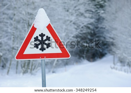traffic sign warns of snow and ice at road - stock photo