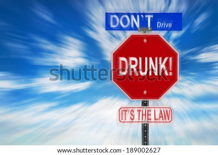 Traffic signs against a cloudy blue sky with the words Don't Drive Drunk, it'??s the Law written on them.  Image is blurred to imply motion and blurred vision due to intoxication.