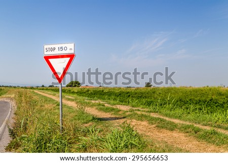 traffic signs and country roads - give way to 150 m signal with an obligation to stop on dirt country road on the bank of a river