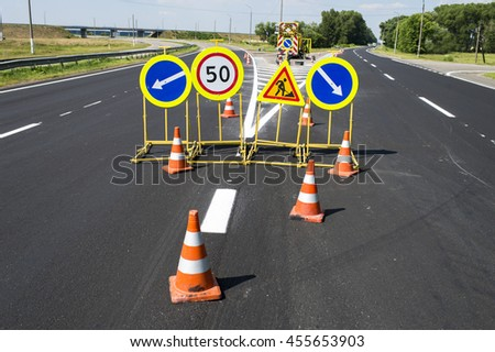 traffic signs during repair and paint work on the fenced road cones