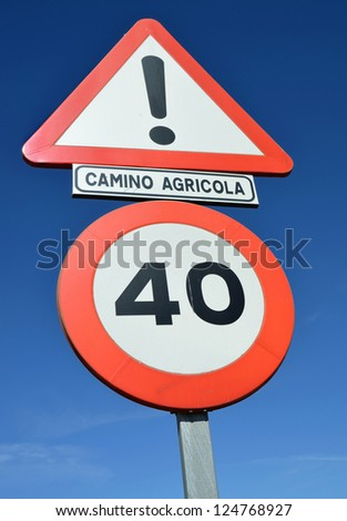Traffic signs on a rural road with various indications isolated against a blue sky