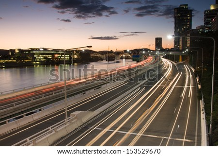 Traffic streams along the Pacific Motorway and Victoria Bridge during rush hour at dusk.
