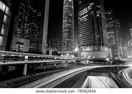 Traffic through downtown in Hong Kong in black and white toned - stock photo