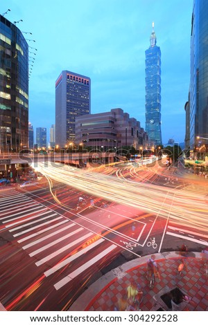 Traffic trails at a busy street corner of Taipei City ~ Xinyi District and downtown area at dusk With landmark of Taipei , Taipei 101  - stock photo