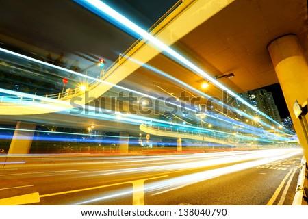 Traffic under the bridge at night - stock photo