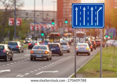 Traffic with cars and bus on city boulevard towards the crossroad with green light opposite the setting sun. Shallow depth of field, focus on blue sign in the foreground. - stock photo