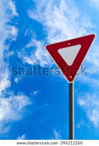 Traffic yield sign against a blue cloudy sky with copy space. Vertical orientation. - stock photo