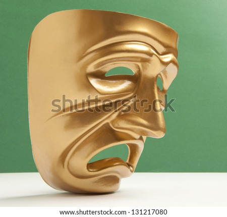 Tragedy theatrical mask on a green background - stock photo