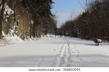 Trail along the Missouri River in the late afternoon in the winter; ski tracks  - stock photo