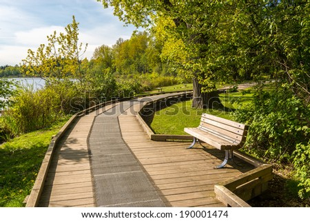 Trail and picnic bench in Deer Lake Park, Vancouver, Canada. - stock photo