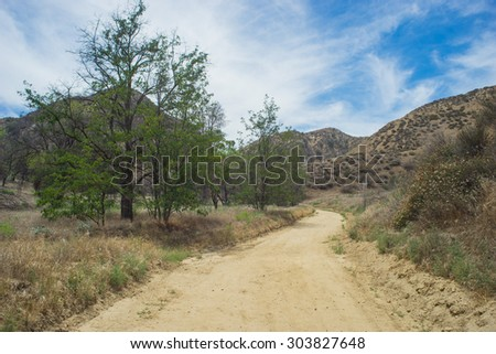 Trail leads through California hills past forest meadow. - stock photo