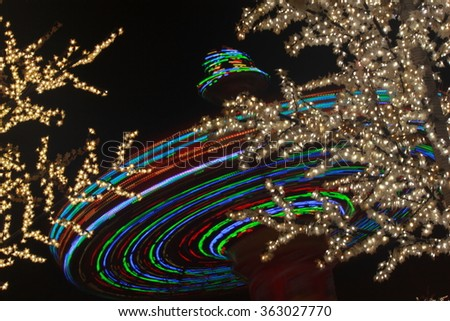 Trail light of  a thrill ride in an amusement park, at night, with a dark black background. - stock photo