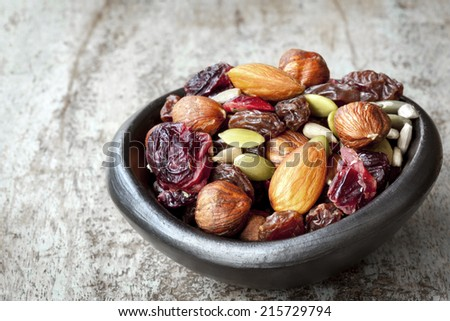 Trail mix in black bowl.  Delicious healthy fruit, nuts and seeds. - stock photo