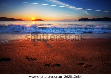 Trail of footprints along a beach shore with crashing waves at sunset with distant cliffs - stock photo