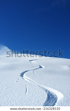 Trail of skis in the snow on a beautiful day - stock photo