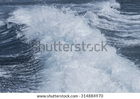 Trail on water surface behind of fast moving  speed boat, view from boat trace in the sea - stock photo