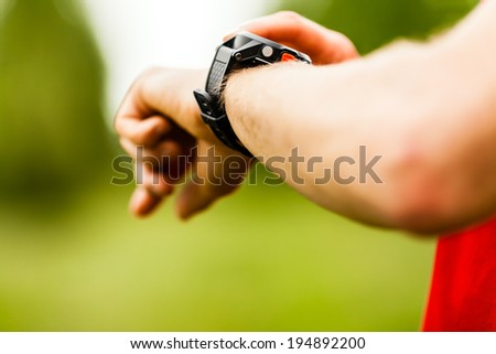 Trail or cross country runner on mountain path looking at sportwatch smart watch, checking performance or heart rate pulse trace. Goal achievement, sport and fitness concept outdoors in nature. - stock photo