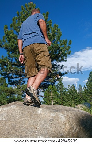 Trail runner climbing a steep rock in his path - stock photo