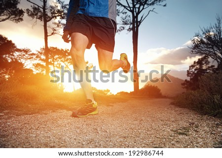 trail runner man exercising for fitness at sunrise in mountains doing sport - stock photo