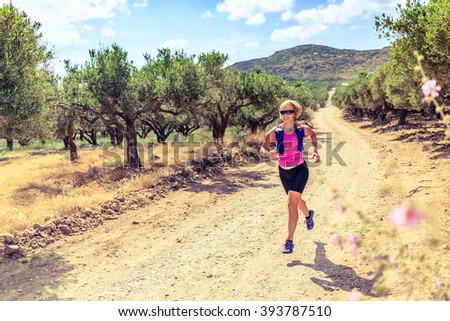 Trail runner woman cross country running on dirt road in mountains on summer beautiful day. Training and working out female jogging and exercising outdoors in nature, olive tree road on Crete, Greece - stock photo