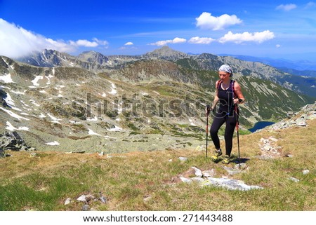 Trail runner woman on sunny mountain slope in summer - stock photo