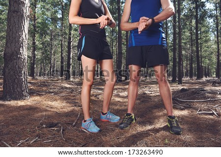 Trail running couple check time on their gps watch for tracking pace - stock photo