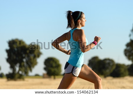 Trail running in country side. Woman runner sprinting and training for cross race. Fitness girl exercising on summer rural landscape. - stock photo