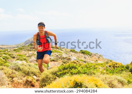 Trail running man cross country running in mountains on summer beautiful day. Training and working out runner jogging and exercising outdoors in nature, rocky footpath on Crete, Greece - stock photo