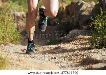 trail running man on mountain path exercising - stock photo