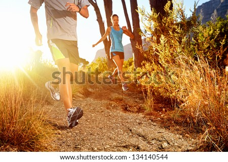 Trail running marathon athlete outdoors sunrise couple training for fitness and healthy lifestyle - stock photo