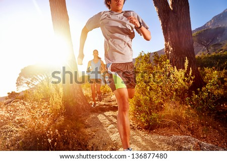 Trail running marathon athlete outdoors sunrise couple training for fitness and healthy lifestyle
