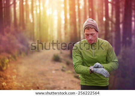 Trail running runner looking at heart rate monitor watch running in forest wearing warm jacket sportswear, hat and gloves. Male jogger running training in woods. - stock photo