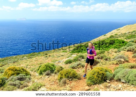 Trail running woman cross country running in mountains, healthy lifestyle on inspirational beautiful day. Motivation, training and working out runner jogging and exercising outdoors on Crete, Greece - stock photo