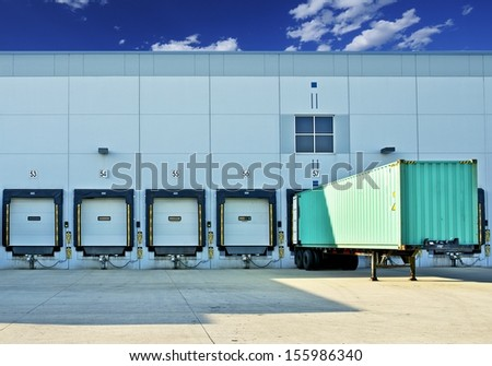 Trailer in a Dock. Warehouse Building with Gates. Business and Logistics Photo Collection - stock photo