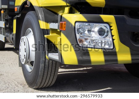 Trailer truck, heavy freight, transportation of large cargoes, modern truck, truck cab, bright paint, horizontal image, the wheel of the truck, the optical lamp on the truck.