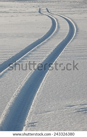 Trails of wheels in fresh snow - stock photo