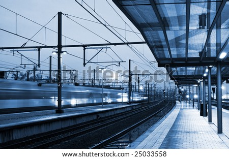 Train coming to the station in twilight (blurred) - tinted blue - stock photo