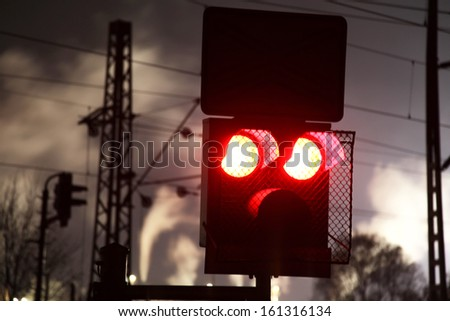 Train crossing and factory at night - stock photo