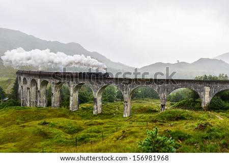 Train crossing the Glenfinnan Viaduct, Scotland, UK - stock photo