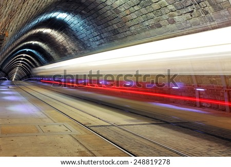 Train disappearing into a tunnel - stock photo